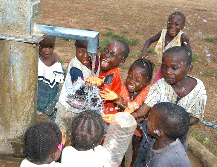 excited children getting clean water from faucet