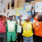 african boys holding books donated by H2H Iintl