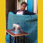 African girl standing in front of sewing machine donated by H2Hintl