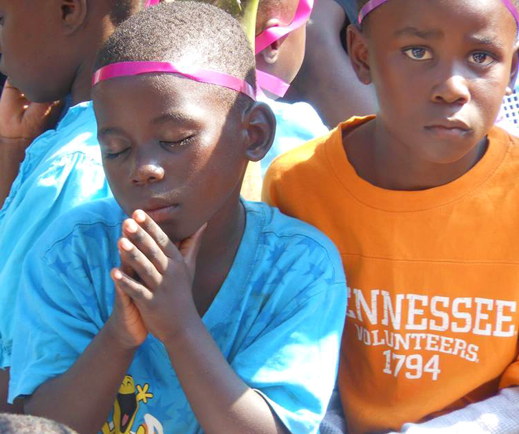boy praying in africa