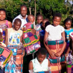 Samson and Gladys posing in Africa with children receiving blankets