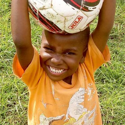 African boy with soccer ball on his head