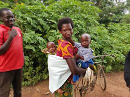 woman in Uganda riding a bike with twins on her back and front