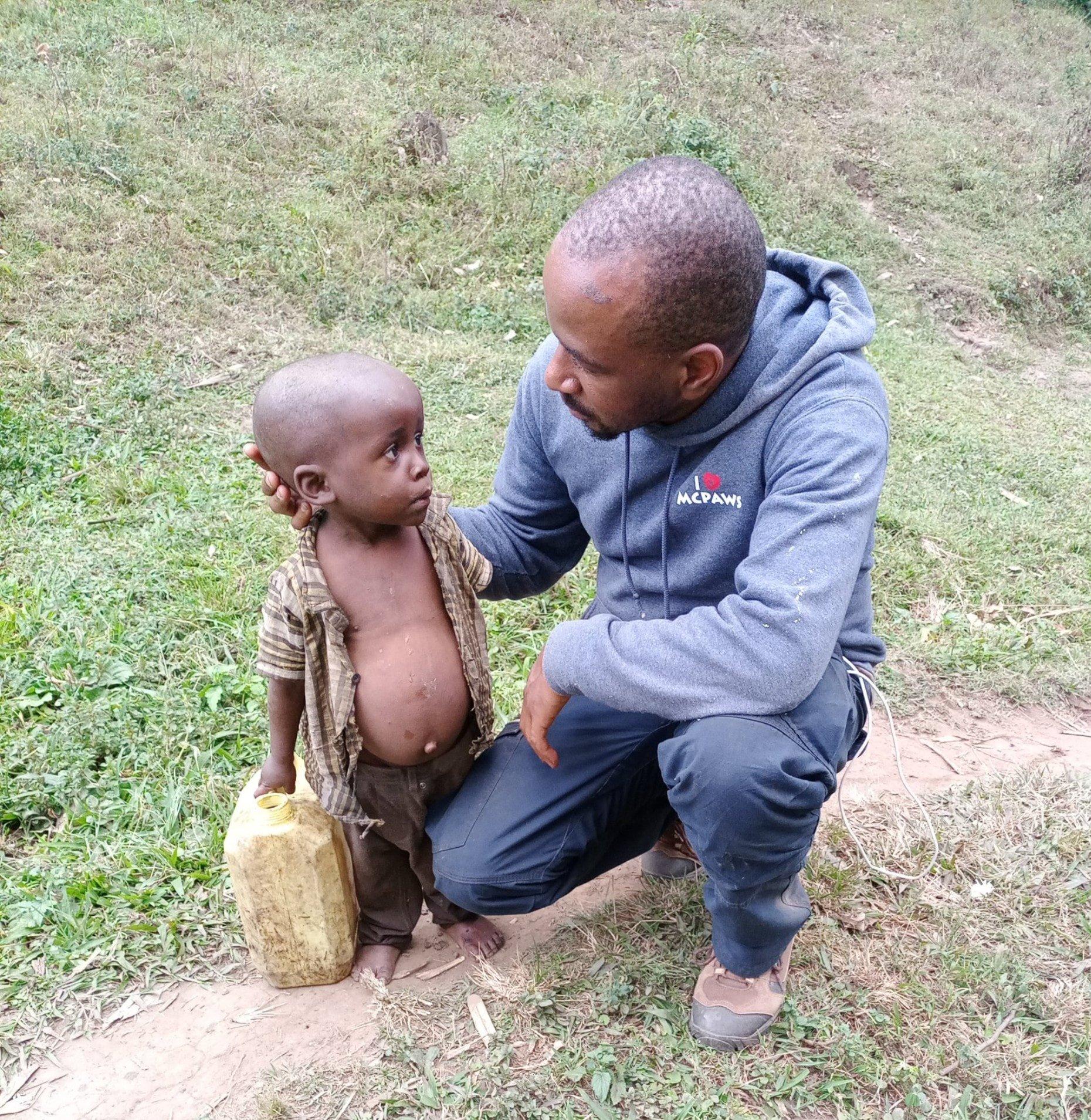 Richard Mwesigwa helping Batwa child